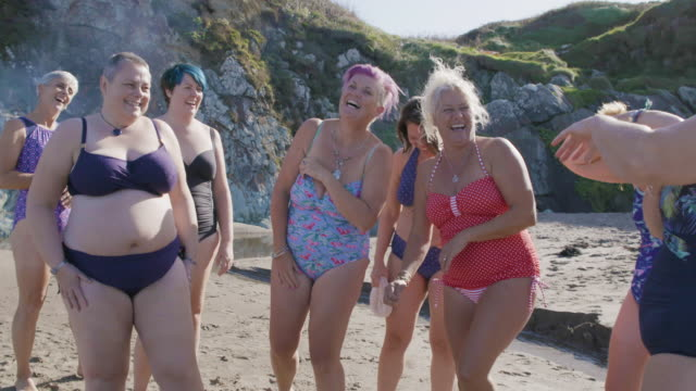 a group of women laughing and having fun together as they get ready for a swim in the sea. - only women stock videos & royalty-free footage