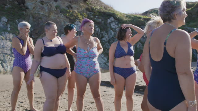 a group of women laughing and having fun together as they get ready for a swim in the sea. - 45 49 years stock videos & royalty-free footage