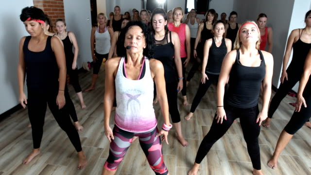 vídeos de stock e filmes b-roll de group of women led by an instructor doing breathing exercises - esforço