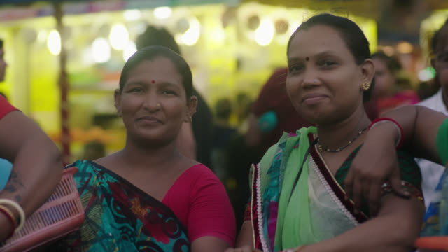 SLO MO. Group of women look at camera and smile in busy Mumbai marketplace.