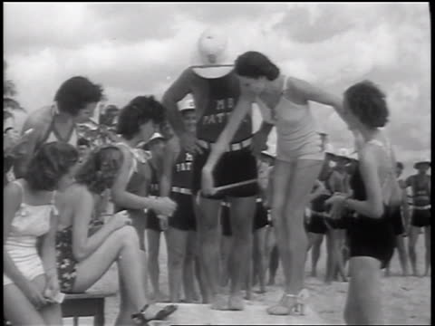 b/w 1937 group of women measuring legs of male lifeguard in beauty contest / florida / newsreel - beauty contest stock videos & royalty-free footage