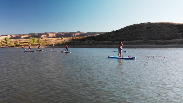 a group of women paddling in a row on paddleboards on a desert lake on a sunny day in western colorado (snooks bottom) - pagaiare video stock e b–roll