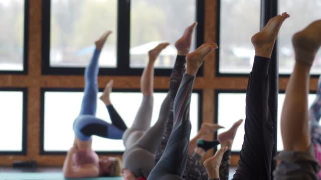 vídeos de stock, filmes e b-roll de grupo de mulheres praticando yoga em aula de yoga - figura feminina