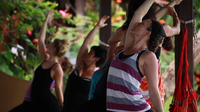 a group of women practising yoga on an outdoor yoga deck surrounded by lush green vegetation and then the yoga teacher/woman corrects their postures - kelly mason videos stock videos & royalty-free footage