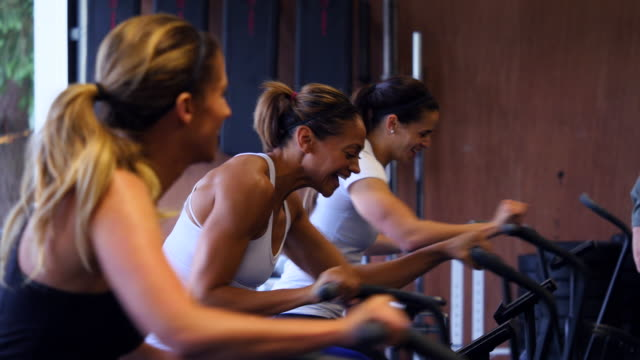 vídeos de stock, filmes e b-roll de ms group of women riding stationary bikes during workout in gym gym - treino cruzado