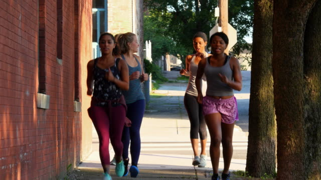 ms group of women running on sidewalk of city street at sunrise - five people stock-videos und b-roll-filmmaterial
