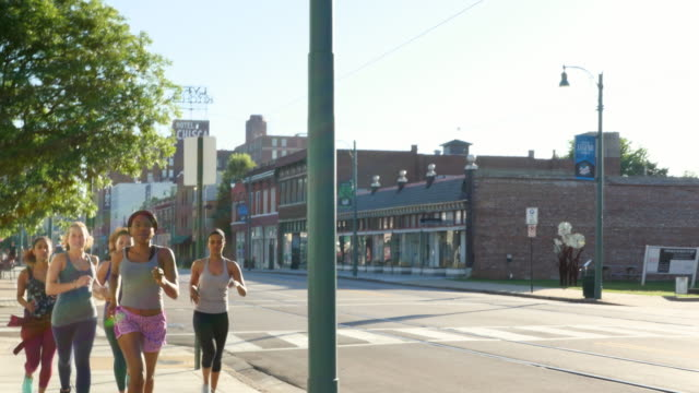 MS Group of women running on sidewalk of city street at sunrise