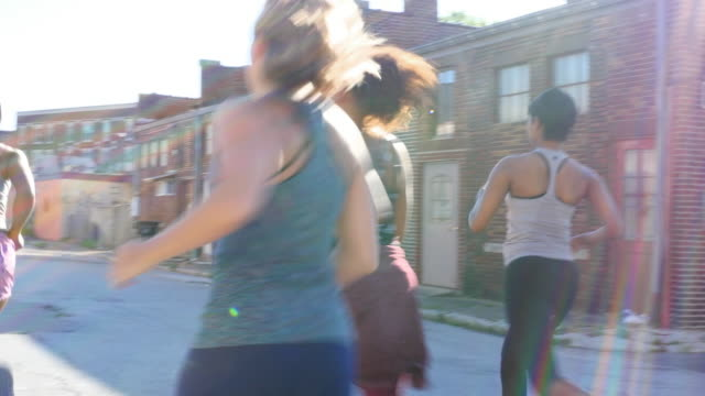 MS Group of women running on urban street at sunrise