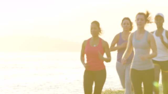 MS group of women running together outdoors at sunset