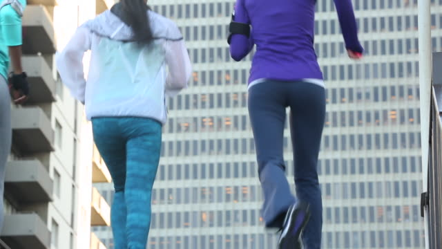 A group of women running together outdoors in a urban area.