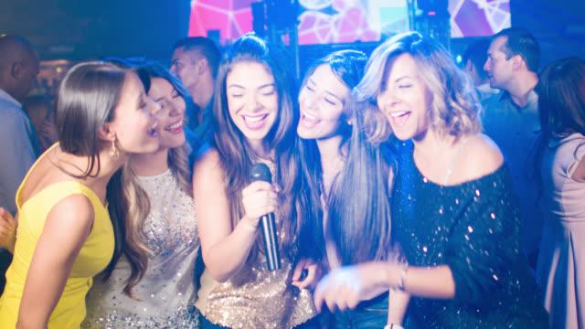 Grupo de mujeres cantando en un bar de karaoke