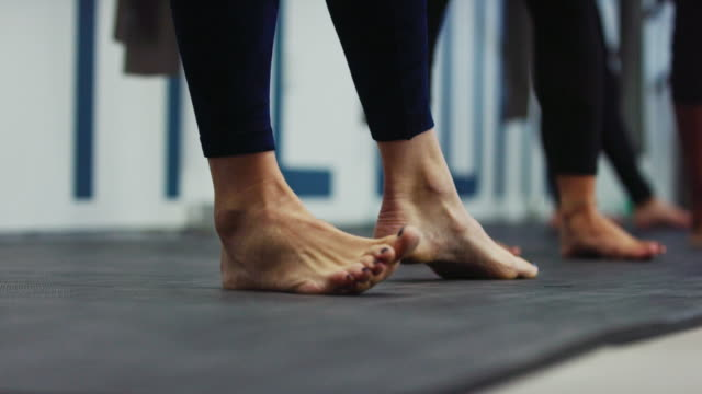 a group of women stretch their legs and feet together at an exercise studio - barefoot stock videos & royalty-free footage