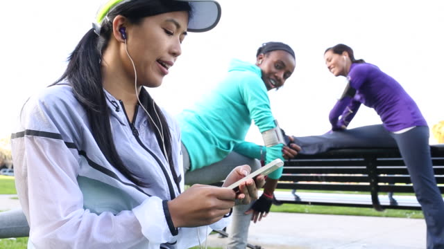 A group of women stretching and talking together before running outdoors in a urban area.