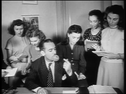 B/W 1947 group of women surround man blowing bubble at desk (Andrew J Paris) / newsreel