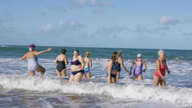 a group of women swimmers laughing and jumping around as they get into the cold sea for a swim. - bonding stock videos & royalty-free footage