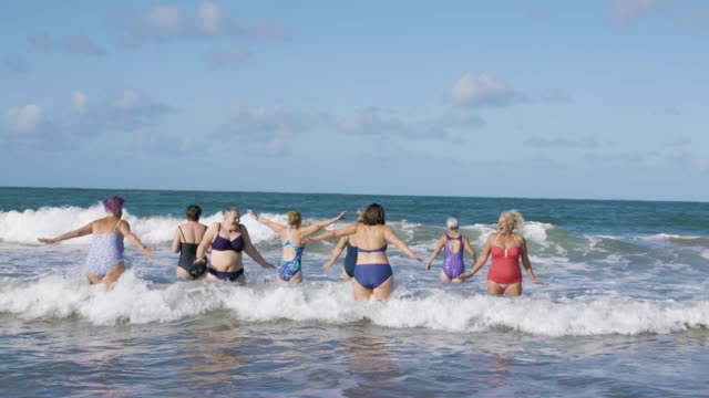 a group of women swimmers laughing and jumping around as they get into the cold sea for a swim. - togetherness stock videos & royalty-free footage