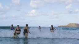 A group of women swimmers laughing and jumping around in the cold sea.