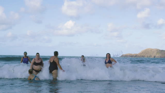 a group of women swimmers laughing and jumping around in the cold sea. - active lifestyle stock videos & royalty-free footage