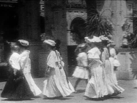 b/w 1905 pan group of women walking toward amusement park / coney island / documentary - coney island brooklyn stock videos & royalty-free footage