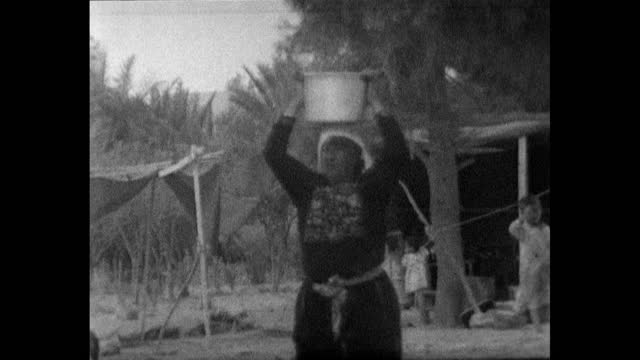 group of women, wearing traditional clothing, carry buckets on their heads in a refugee camp in jordan; 1967. - simple living stock videos & royalty-free footage