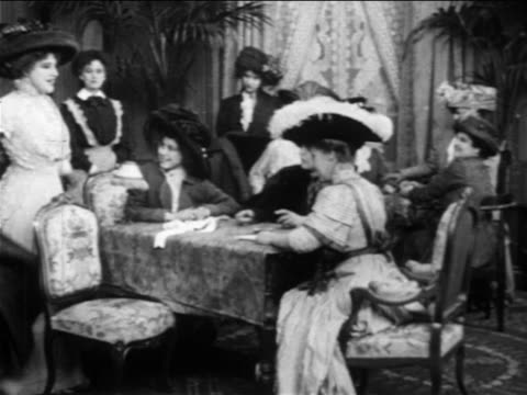 b/w 1909 group of women with large hats sitting + playing bridge while talking + laughing - 1900 1909 stock-videos und b-roll-filmmaterial