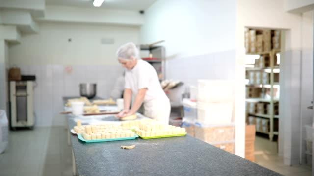 vidéos et rushes de groupe de femmes qui travaillent à la production de boulangerie - charlotte médicale ou sanitaire