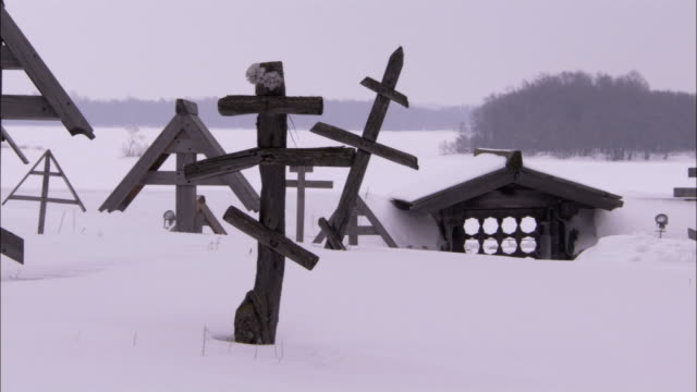 A group of wooden grave markers stand in the snow near the Church of the Transfiguration. Available in HD.