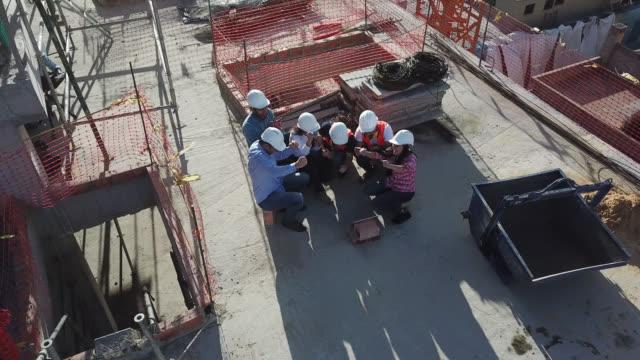 vídeos y material grabado en eventos de stock de grupo de trabajadores en una construcción tomando un descanso viendo un partido de la copa del mundo en una tableta digital - vista aérea - eufórico