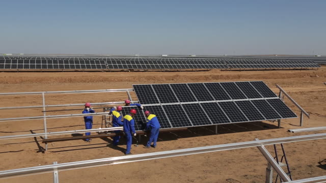 vídeos de stock e filmes b-roll de group of workers installing solar panels at the yashkul solar plant, operated by hevel group. the european union's climate chief says rising demand... - enfeites para a cabeça