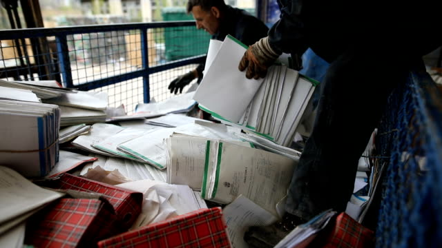 gruppe von mitarbeitern, die papiere in recyclinganlage sortieren - papier stock-videos und b-roll-filmmaterial