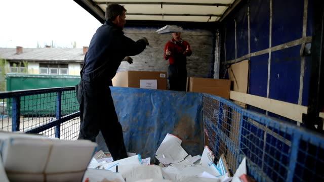gruppe von mitarbeitern, die papiere in recyclinganlage sortieren - arbeitsintensive produktion stock-videos und b-roll-filmmaterial
