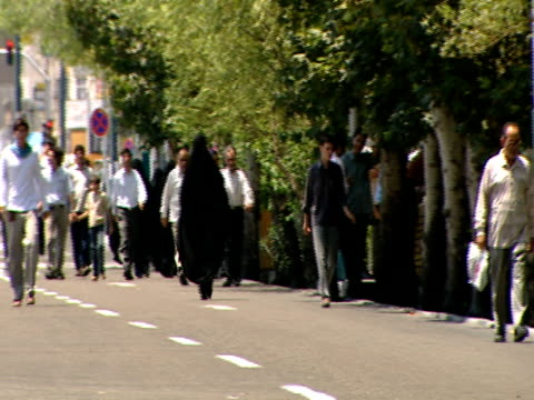group of worshipers walking on street toward midday prayer / qom, iran - credente video stock e b–roll
