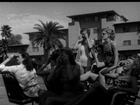 Group of young adult females in bathing suits sitting by pool one woman checking watch all putting on eye protection small sunglasses looking left...