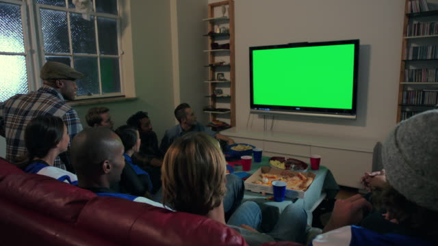 group of young adult males and females together celebrate watching sports on tv wide shot static - television chroma key stock videos & royalty-free footage