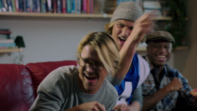 group of young adult males celebrate watching sports on tv medium shot - play fight stock videos and b-roll footage