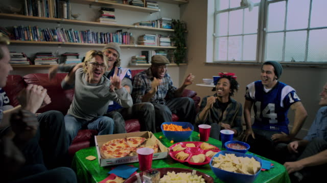 Group of young adult males celebrate watching sports on TV wide shot tracking IN
