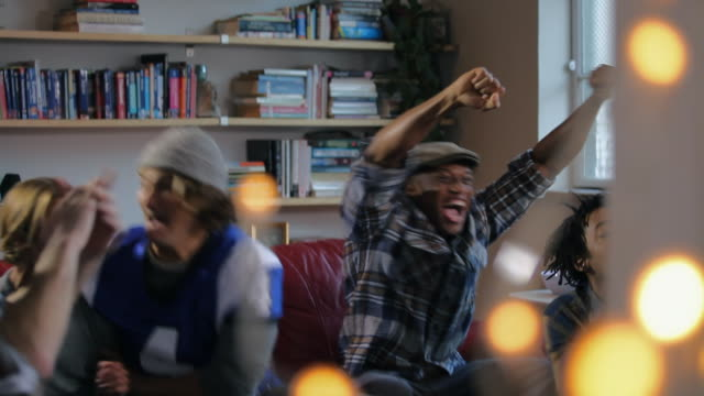vidéos et rushes de group of young adult males together celebrate watching sports on tv - prise de vue en intérieur