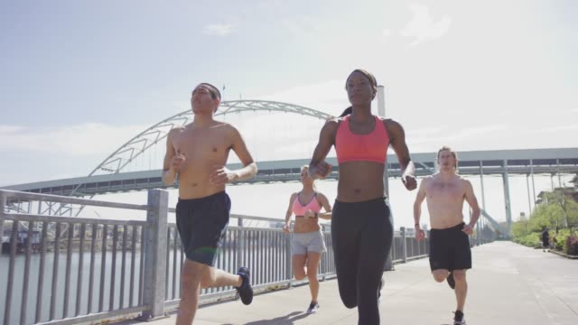 Group of young adult runners running in the city along the waterfront