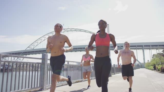 Groupe de jeunes adultes, les coureurs courir dans la ville le long du front de mer
