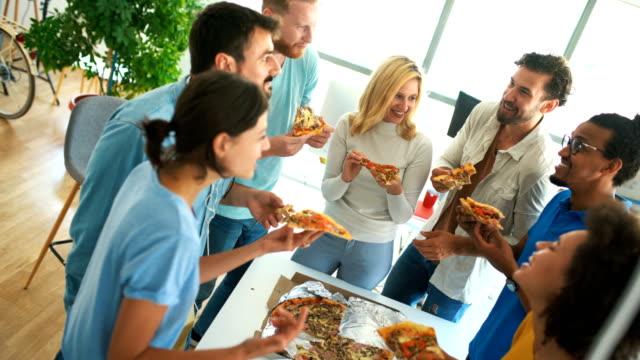 vídeos de stock e filmes b-roll de group of young adults having pizza. - hora de almoço