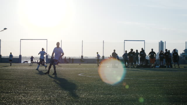 A group of young adults play soccer at sunset - summer 2016 - 4k