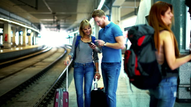 group of young adults waiting for a train. - stazione video stock e b–roll