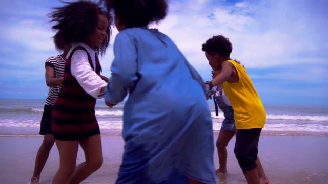 vídeos de stock, filmes e b-roll de group of young african american children running and are join hands on the beach. - miscigenado