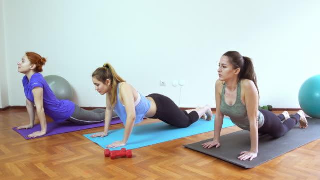Groep van jonge en aantrekkelijke vrouwen oefenen op yoga mat