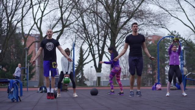 group of young and sporty people training outdoors with jumping rope and kettlebell - warm up exercise stock videos & royalty-free footage