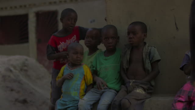 Group of young Angolan children sit outside
