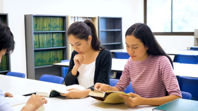 Group of young Asian student with book and doing research in college library, learning education and school concept