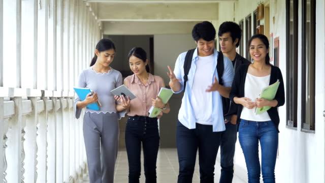 stockvideo's en b-roll-footage met groep jonge aziatische studenten tieners met school map studeren leesboek gonna klas op campus. onderwijs en tiener concept - brochure