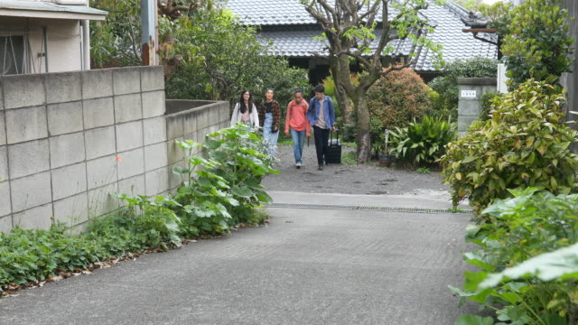 Group of Young Asian Tourists Leaving a Ryokan Inn