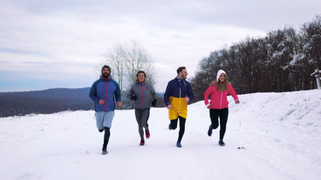 Group of young athletes jogging outdoors during cold winter day.
